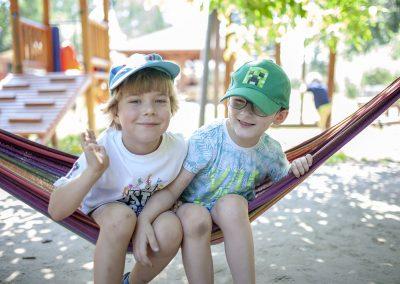 Rekrutacja. Uśmiechnięci chłopcy na placu zabaw przedszkola Róża Montessori w Warszawie Białołęce